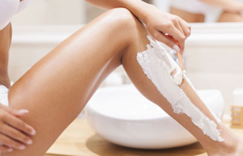 young lady wet shaving legs
